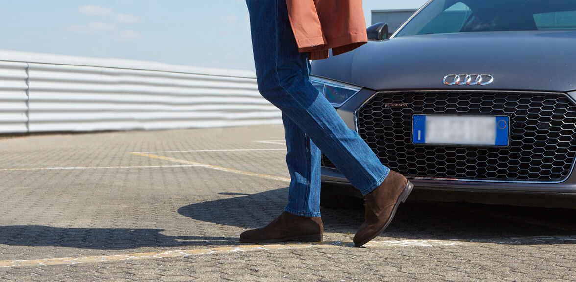 Model wearing dark brown suede ankle boots for men, with a luxury car in the background, by Fragiacomo