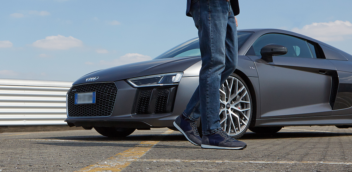 Model wearing Fragiacomo blue suede leather sneakers, with a luxury car in the background