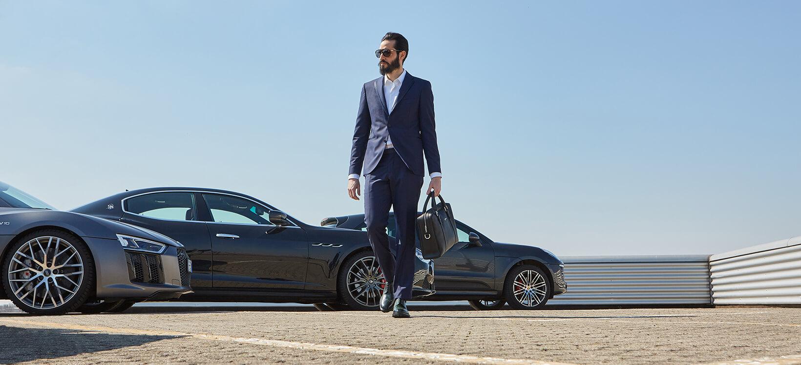 Francesine Brogue in pelle di vitello colore verde smeraldo e borsa da lavoro in pelle nera con dettagli argentati indossate da un uomo vestito elegante in piedi mentre cammina