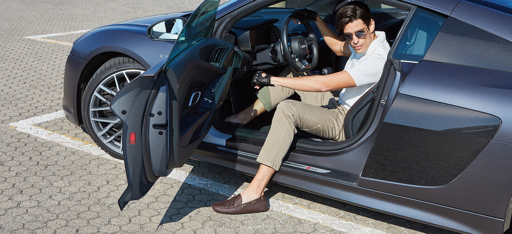 Brown deerskin driving shoes worn by a man dressed in casual style while getting out of a luxury car