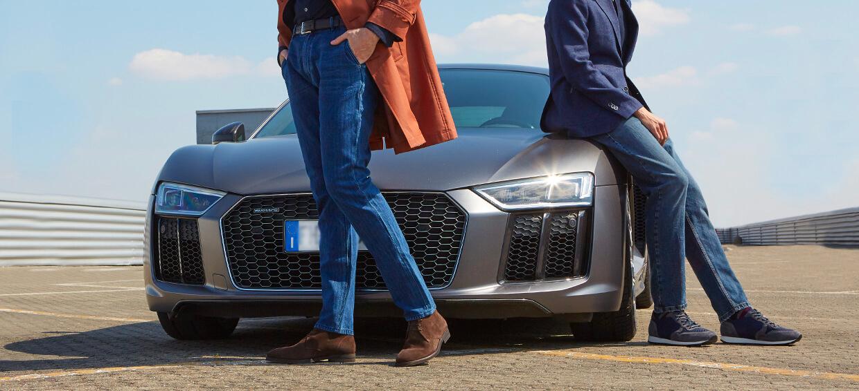 Modelli che indossano un paio di polacchine scamosciate testa di moro e un paio di sneaker in pelle blu da uomo con sullo sfondo una macchina di lusso, by Fragiacomo