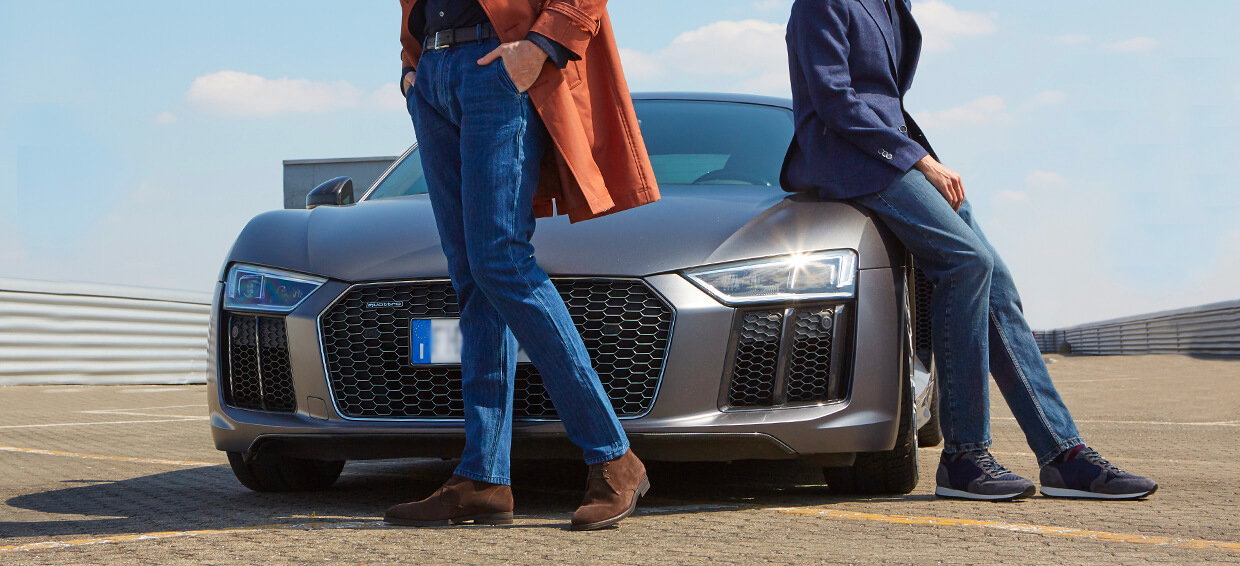 Models wearing dark brown suede ankle boots and blue leather men's sneakers with a luxury car on the background, by Fragiacomo
