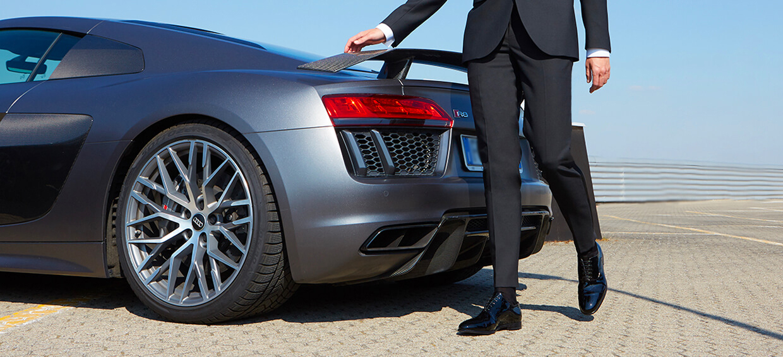 Modello che indossa francesine in vernice nera di lusso da uomo, con sullo sfondo una macchina, by Fragiacomo