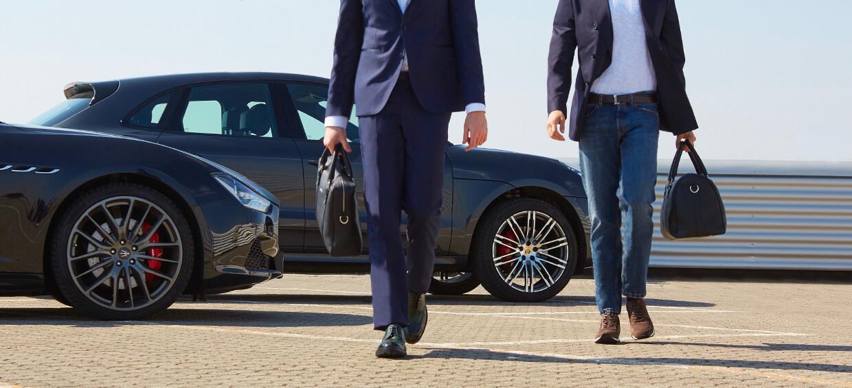 Modelli che indossano un paio di sneaker in pelle marrone e un paio di derby verde scuro brogue da uomo con sullo sfondo macchine di lusso, by Fragiacomo