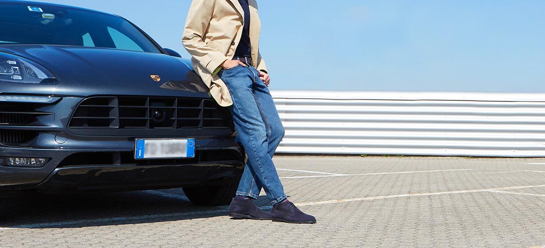 Modello che indossa polacchine blu scamosciate da uomo, con sullo sfondo una macchina di lusso, by Fragiacomo