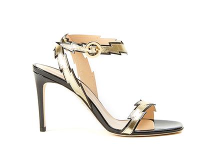 Sandali alti dal design elegante e seducente, realizzati in vernice nera e decorati con cinturini color oro in pelle laminata a forma di fulmine by Fragiacomo